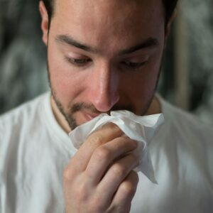 Person blowing their nose from histamine intolerance